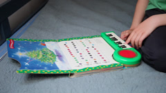 Little boy sits in bed, child playing Christmas Carol to a music book, keyboard - stock footage