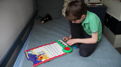 Boy sits in bed, child playing Christmas Carol to a music book, keyboard - stock footage