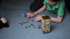 Boy counting coins, child puts money in a piggy bank, kid saving money Stock Footage
