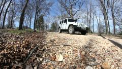 White Jeep coming down road - low and wide angle Stock Footage