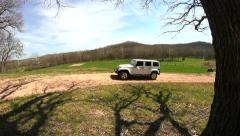 Slider shot from tree to white Jeep Stock Footage