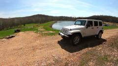 Slider shot of white 2014 Jeep with lake in background Stock Footage