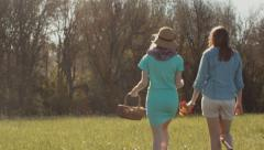 2 Girls Look For A Spot To Have A Picnic In A Field, On A Beautiful Spring Day Stock Footage