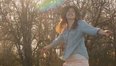Closeup Of Young Woman Twirling In A Field And Tossing Her Hat In The Air Stock Footage