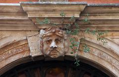 Stucco mask on the facade - stock photo