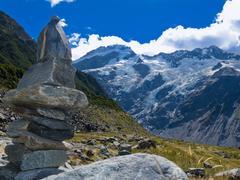 hooker valley rock cairn aoraki mt cook trail nz - stock photo