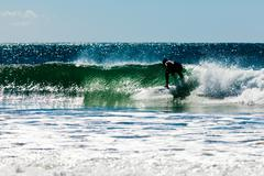 Surfboard surfer rides wave ocean surf Stock Photos
