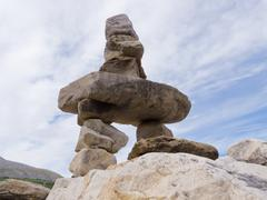 cairn trail marker inuksuk large stacked stones - stock photo