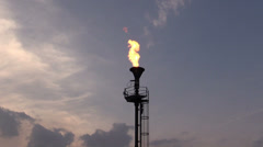 Oil burning torch against the sunset sky - stock footage