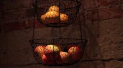 Apples And Oranges hanging in a basket Stock Footage