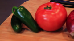 Tomatoes and Jalepenos on a wooden cutting board Stock Footage
