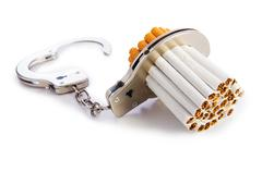 Addition concept with cigarettes and handcuffs - stock photo