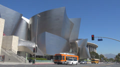 Walt Disney Concert Hall traffic car street stop red light bike pass school bus  Stock Footage