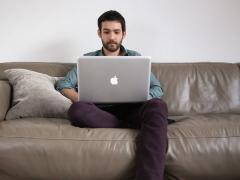 Young man reading interesting story on laptop Stock Footage