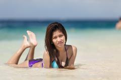 filipina woman lying on sand - stock photo