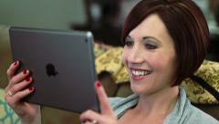 Attractive woman watches video on tablet and smiles - stock footage