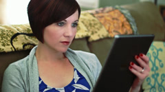 Woman types on her tablet - stock footage