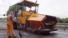 Paver (asphalt) machine slowly crawling by Stock Footage