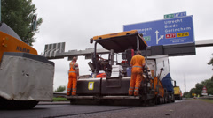 Asphalt machine laying a fresh layer of asphalt with roller machine behind Stock Footage