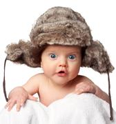 Sweet little baby in a huge fur hat Stock Photos