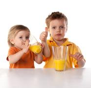 happy children drink orange juice isolated on white - stock photo