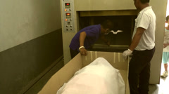 Worman's corpse placed inside cremation chamber Stock Footage