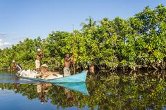 Malagasy people paddling Stock Photos