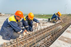 Workers mount bridge span - stock photo
