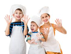 Three young chefs with hands in flour - stock photo