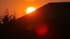 Sun setting down behind the house roof near tree, sunset, close-up Stock Footage
