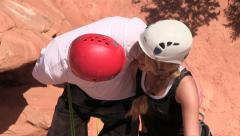 Rappelling couple stops on cliff to hug and kiss Stock Footage