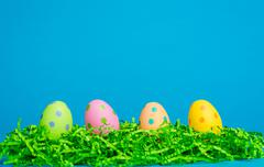 4 assorted color easter eggs on a sky blue background - stock photo