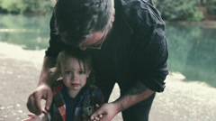 Father Consoles Son And Brushes Dirt Off His Hands After A Fall - stock footage
