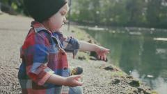 2 Year Old Boy Sits On A Bank, Throws Pebble Into Water, Then Walks Away Stock Footage