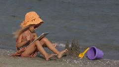 Child on Tablet on Beach, Little Girl Playing on Seashore, People, Children Stock Footage
