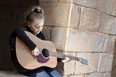 A girl learning or practicing on a musical instrument, a guitar Stock Photos