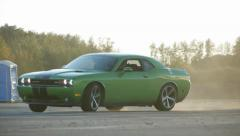 Green Dodge Challenger drifting around a corner. - stock footage