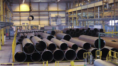 Workers loading big pipe with crane on tube-rolling plant warehouse, Russia Stock Footage
