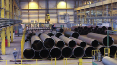 Workers stacking big pipes with cranes at tube-rolling plant warehouse, Russia Stock Footage