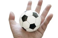 Stock Photo of football toy in hand isolated
