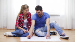 Smiling couple discussin blueprint at home Stock Footage