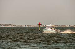 Moving fishing power boat in a distance on the ocean Stock Photos