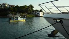 Landed yacht and small yellow fisherman boat; Peaceful, sunset Cesme, izmir Stock Footage
