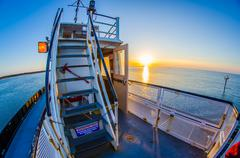 riding on a ferry boat at sunset - stock photo