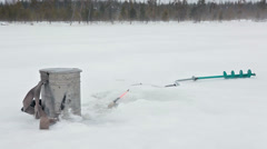 Ice drill, steel box and fish-rod laying on snow when blizzard at winter lake Stock Footage
