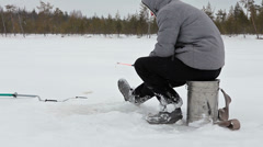 Lonely fishman at ice fishing sitting with rod, winter in Russia Stock Footage