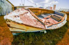 old rotten abandoned row boat on land - stock photo