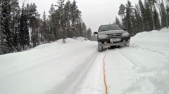 Low point view of towing a broken down car on a winter forest road Stock Footage