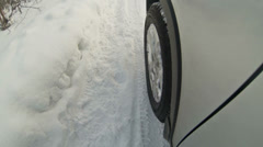 Car side mounted camera and wheel driving over snowdrift Stock Footage
