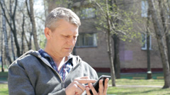Mature man with the smartphone on the street Stock Footage